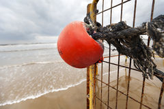 Winter Beach Buoy and Fence. Wide angle close-up of an old red buoy hanging from a corroded fence on a black sand covered rope, located at the beach on an Stock Photography