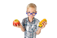Wide angle close-up portrait of boy a student in shirt in glasses hugging apple and schoolbus in hands, looking at camera, isolate Stock Image