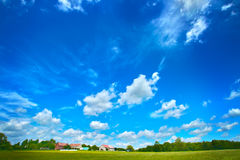 Wide angle clouds over green meadow Stock Photography