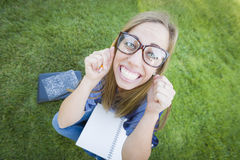 Wide Angle of Excited Student Wearing Eyeglasses with Books and Pencil Royalty Free Stock Photography
