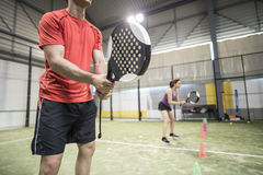Wide angle image of couple training in paddle tennis class behin Stock Photo