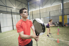 Wide angle image of couple training in paddle tennis class behin Royalty Free Stock Image