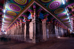 Wide angle from inside the meenakshi temple in madurai india, with colorful ceiling and columns. And a long exposure to blur the pilgrims walking by Stock Images