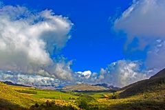 Wide-angle landscape of  mountains and clouds. Wide-angle landscape of  fruit plantation with distant mountains and clouds on mountain plateau above Piketberg stock photos
