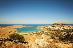 A wide angle vertical landscape view and a shot from a mountain to a little village Lindos in Rhodes, Greece and there`s sail boat. A wide angle vertical royalty free stock images