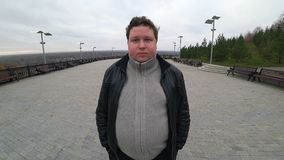 Wide angle lens: young fat man looking at camera, smiling and nods his head YES
