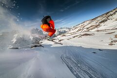 Wide angle male skier in orange suit makes a jump from a snowy ledge in the mountains. Snow powder trailing behind the. Athlete