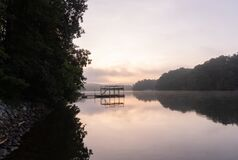 Free Wide Angle Of A Dock At Sunrise With Fog On The Water On Lake Lanier In Georgia And A Rocky Shore Royalty Free Stock Photo - 197330865