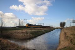 Wide angle overview of a koploper ICM intercity train on the track fron the hague heading to Gouda. Wide angle overview of a koploper ICM intercity train on the stock photography