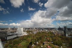 Wide angle overview at 100 metres height over the Rotterdam Skyline with blue sky and white rain clouds. Seen from the Euromast Royalty Free Stock Images