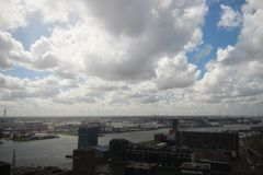 Wide angle overview at 100 metres height over the Rotterdam Skyline with blue sky and white rain clouds. Seen from the Euromast Stock Images