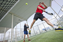 Wide angle paddle tennis action. Wide angle paddle tennis couple smashing ball in court stock photo