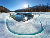 Wide-angle panorama of man on ice melting river.  Stock Photo