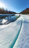 Wide-angle panorama of man on ice melting river.  Royalty Free Stock Photo