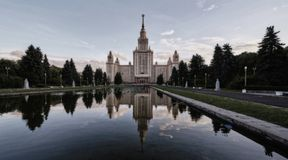 Wide angle panoramic view of sunset campus of Moscow university in spring with water reflections. Soften wide angle panoramic view of sunset campus of Moscow stock photo