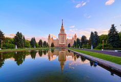 Wide angle panoramic view of sunset campus of Moscow university  under dramatic sky in spring with water reflections. And swimming red ducks stock photos