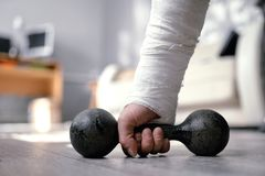 Wide angle photo of broken fractured hand in plaster cast holding dumbbell. Home trainig rehabilitaion after accident. Wide angle photo of broken fractured hand royalty free stock photo