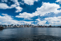 Skyline In Denim. Wide-angle photograph of New York City skyline, featuring Empire State Building, with Hudson River in foreground and sweeping cloudy sky Royalty Free Stock Images