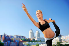 Wide angle picture of a woman practicing king dancer yoga pose Royalty Free Stock Photos
