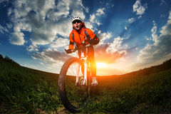 Wide angle portrait against blue sky of mountain biker Cyclist. Low, wide angle portrait against blue sky of mountain biker. Cyclist in red sport equipment Stock Photography
