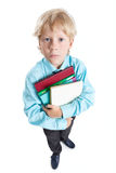 Wide angle portrait of  boy student in blue shirt hugging books in hands, looking at camera, isolated on white background Royalty Free Stock Photos