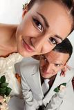 Wide angle portrait of newly-married couple. On the white background, humorous concept Royalty Free Stock Photo