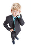 Wide angle portrait of pretty blond boy in suit and tie talking by cellphone, isolated white background Stock Photo