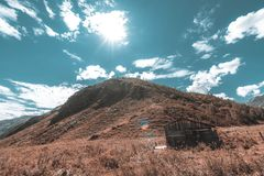 Forsaken cabin in mountains. Wide-angle shooting of abandoned wooden shack or shepherd`s house surrounded by mountains and hills of Altai, native grasses of Royalty Free Stock Photos