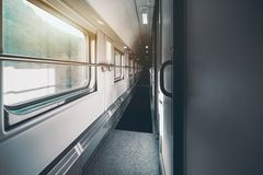 View of second floor interior of double-decker passenger train. Wide-angle shooting of long and empty double-decker passenger train interior with multiple closed Royalty Free Stock Image