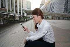 Wide angle shot of attractive young Asian business woman looking mobile smart phone in her hands at outside office with copy space stock photo