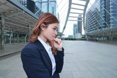 Wide angle shot of attractive young Asian business woman in suit thinking about her job at urban building background. Wide angle shot of attractive young Asian Stock Photos