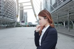 Wide angle shot of attractive young Asian business woman in suit thinking about  job at urban building background. Wide angle shot of attractive young Asian Stock Photos