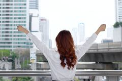 Wide angle shot of back view attractive young Asian businesswoman standing and stretching arms at urban building public background Royalty Free Stock Photos