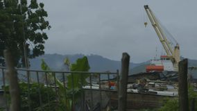 View of cargo ship from village. A wide angle shot of a cargo ship at a distance from village docked at port stock video footage