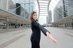 Wide angle shot of cheerful Asian businesswoman extend hand to camera at urban city background. Partnership business concept stock image