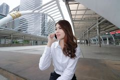 Wide angle shot of cheerful young Asian woman talking on phone at outside office background. royalty free stock image