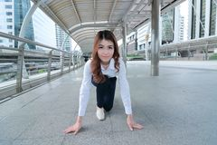 Wide angle shot of confident young Asian woman in start position ready to run at sidewalk of office background. Competition busine. Ss concept Stock Image