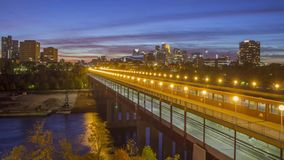 A wide angle shot of downtown Minneapolis over the illuminated Washington Avenue Bridge Spanning the Mighty Mississippi River duri. A twilight wide angle shot of stock footage