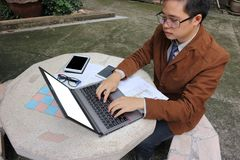 Wide angle shot of handsome yong business man is using laptop with blank screen for his work at outdoor. Wide angle shot of handsome yong business man is using Royalty Free Stock Photos