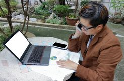 Wide angle shot of handsome young businessman is talking on the phone for his work with laptop and paperwork at public outdoor. Wide angle shot of handsome Royalty Free Stock Photo