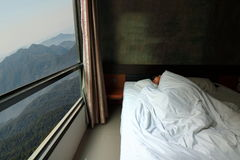 Wide angle shot of handsome young man sleeping comfortably in the bed with beautiful mountain nature morning view from  windows Royalty Free Stock Image
