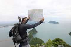 Wide angle shot of hipster young Asian man with backpack standing on the stone and exploring map on the mountain Royalty Free Stock Photos