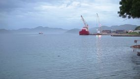 Wide angle shot of a red crane. A wide angle shot of a red crane on a dockyard with container stock video footage
