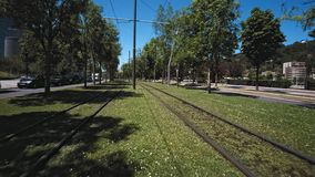 Wide angle shot of train tracks in grass. Camera slowly flies along the tram or train tracks running on grass lawn in middle of futuristic city with ecological stock footage