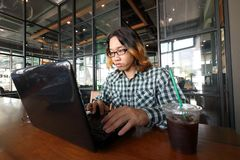 Wide angle shot of young Asian hipster man working against laptop in his office. Stock Image
