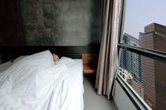Wide angle shot of young Asian man comfortable sleeping with mask on the bed in bedroom Royalty Free Stock Photo