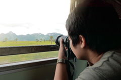 Wide angle shot of young Asian tourist taking a photo of scenic nature mountain with professional camera in the train stock photography