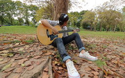 Wide angle shot of young man is leaning to play acoustic guitar at the park Royalty Free Stock Photo