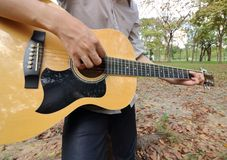 Wide angle shot of young man is leaning to play  acoustic guitar at the park. Stock Images