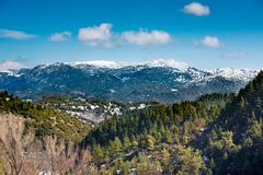 A wide-angle sunny,autumn midday view of snow coated Helmos moun. Tain which located in Peloponnese. Grecce.The photo taken from the opposite mountain named Royalty Free Stock Images